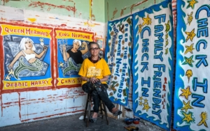 A woman sits on a stool in a room covered with bright, beautiful murals and other art.