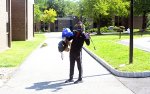 A student in a mask holds up bags.