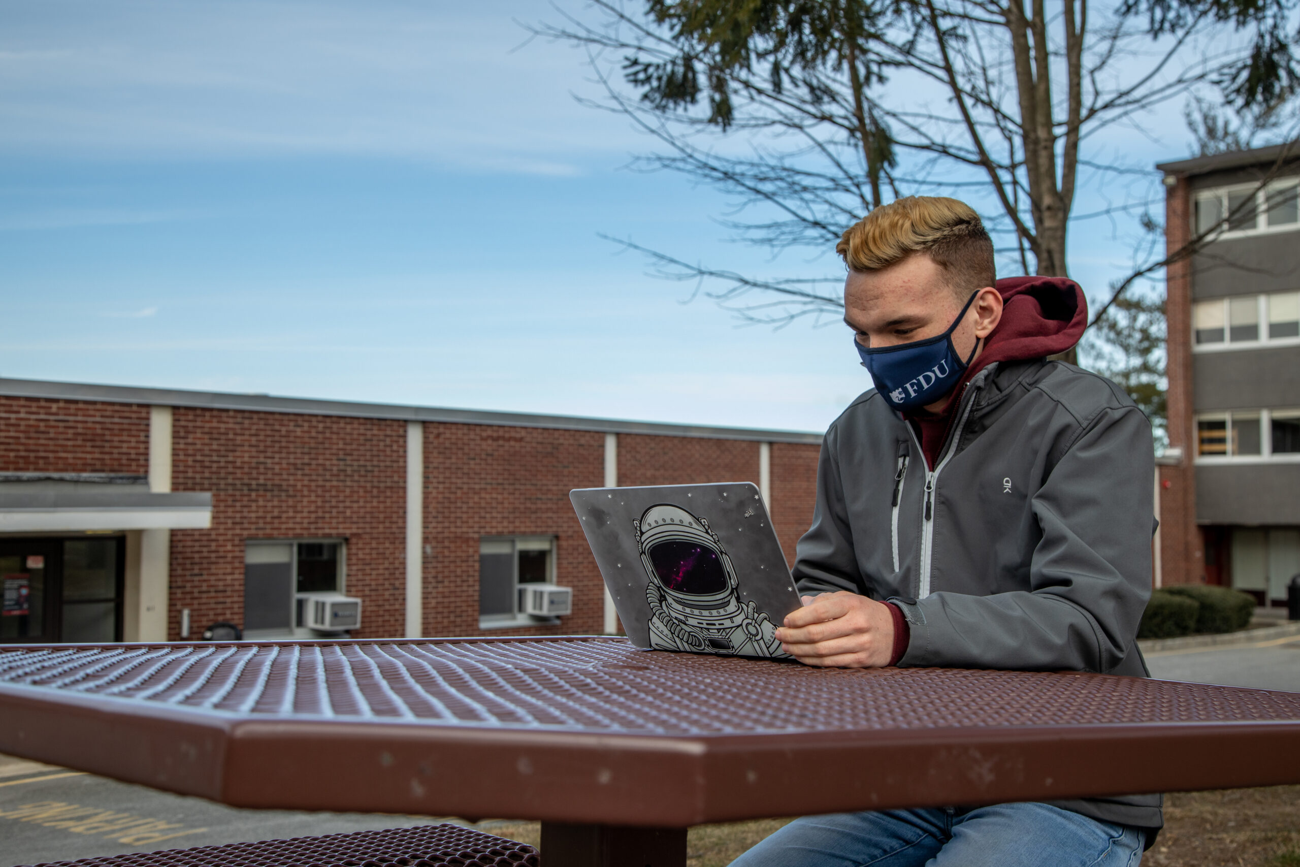 A student works on a laptop wearing an FDU mask.