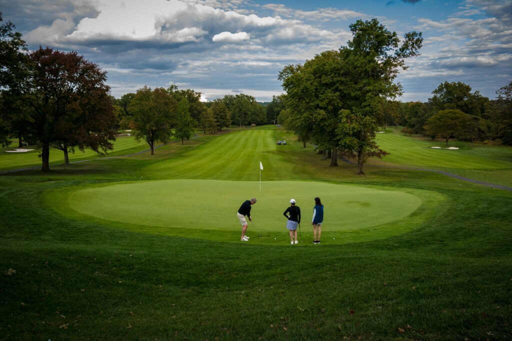 Golfers putting on a golf course green.