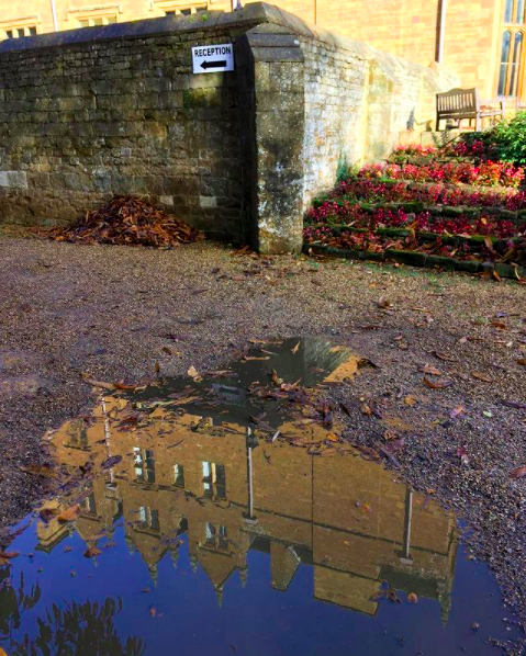 A puddle clearly reflects an image of Wroxton Abbey.