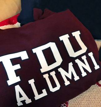 A pile of FDU-branded alumni gear, including a sweatshirt and a hat.