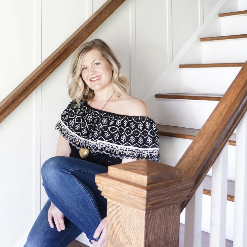A woman sits on a wooden staircase.