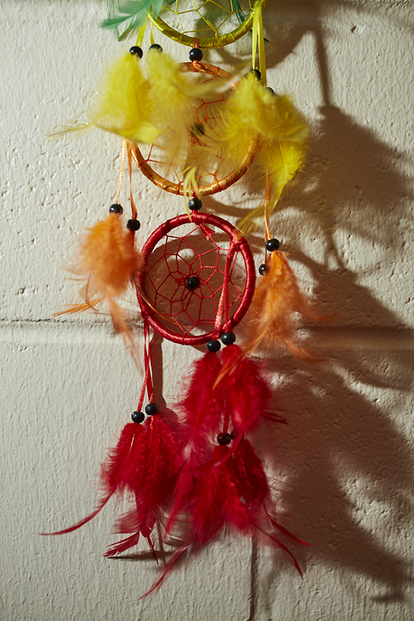 A colorful dream catcher hands on a wall.