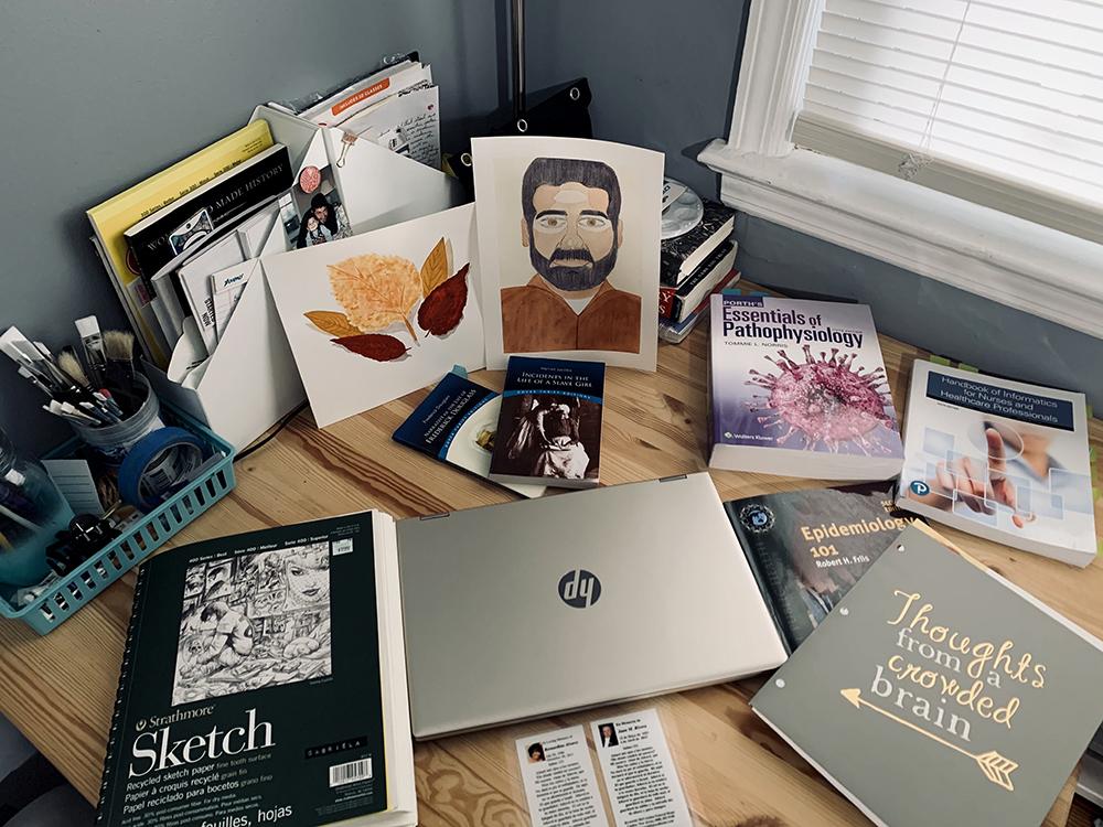 Textbooks, art supplies and a laptop adorn a student desk.