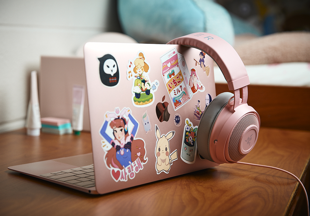 A pink laptop computer, with pink headphones draped over the side, features lots of stickers.