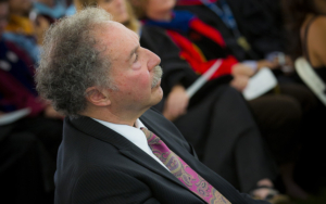 A man in a suit sits in a crowd at convocation.