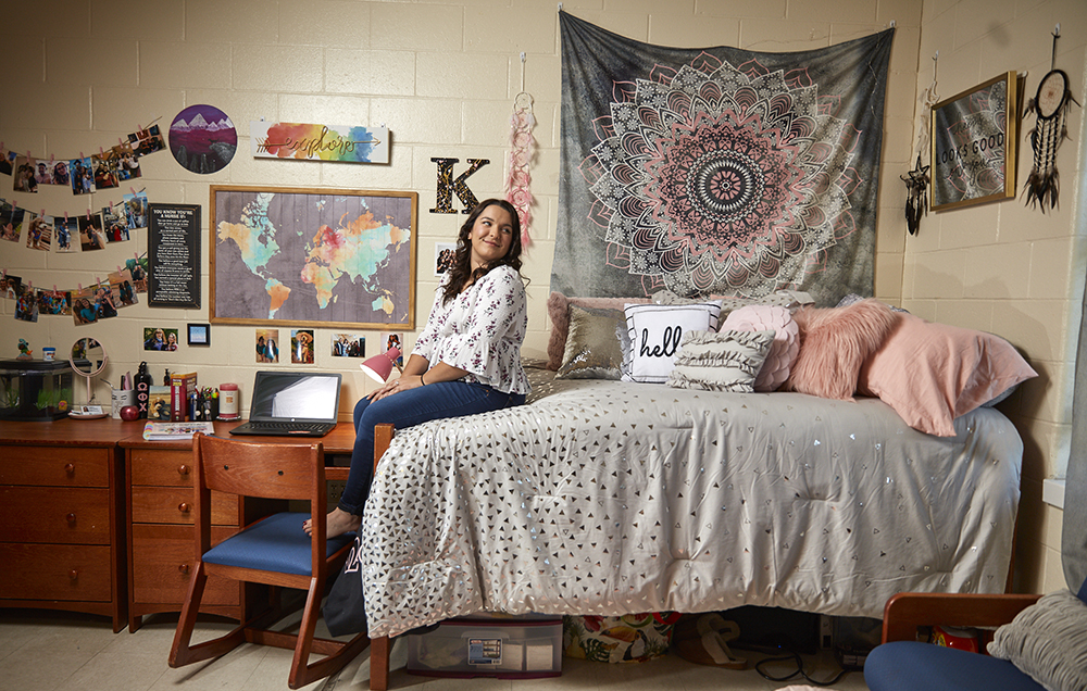 A young woman sits on the edge of her bed in a brightly decorated dorm room.