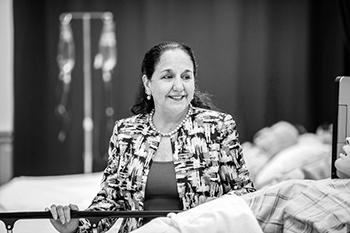Portrait of a woman standing amid nursing equipment.
