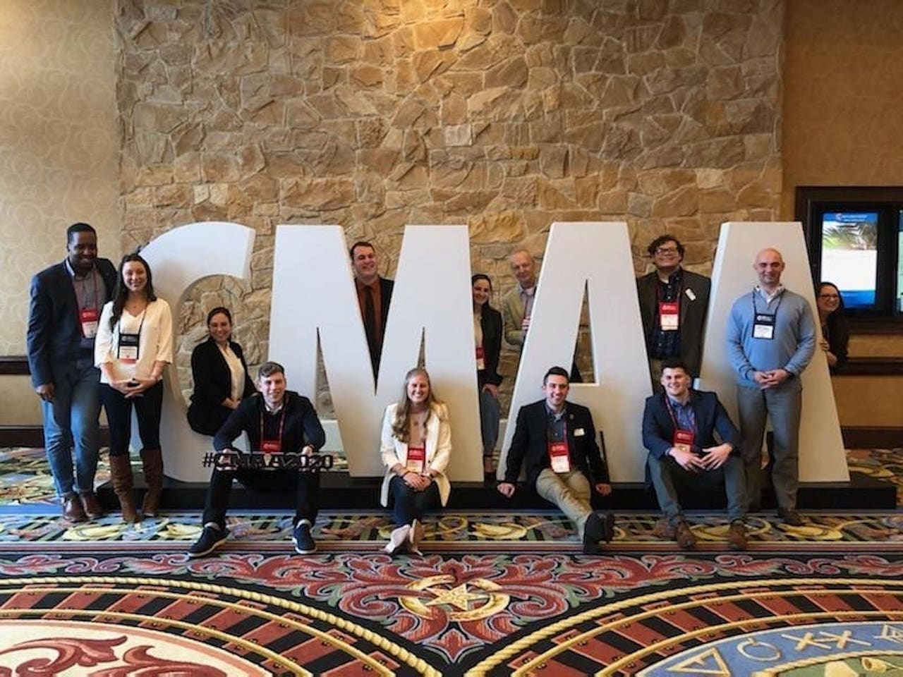 """FDU CMAA members pose in front of letters that spell """"CMAA."""""""