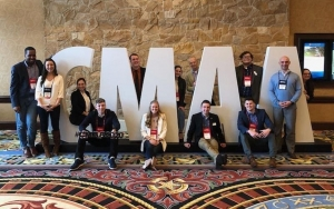 "FDU CMAA members pose in front of letters that spell ""CMAA."""