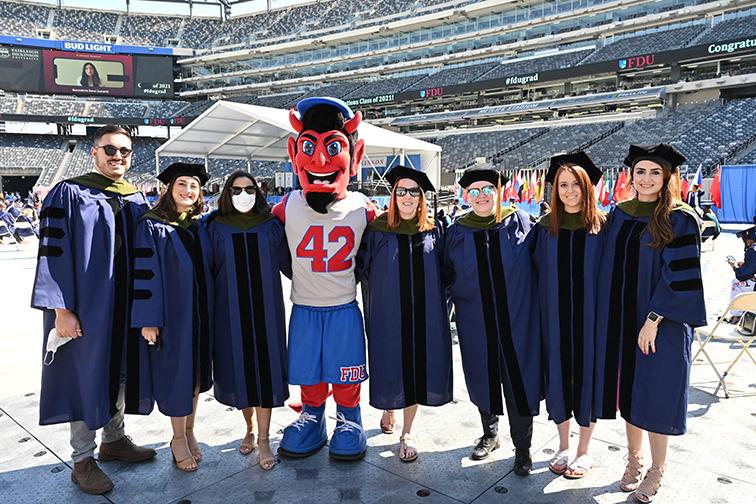 Graduates strike a pose with Ian the Devil, the Florham Campus mascot.