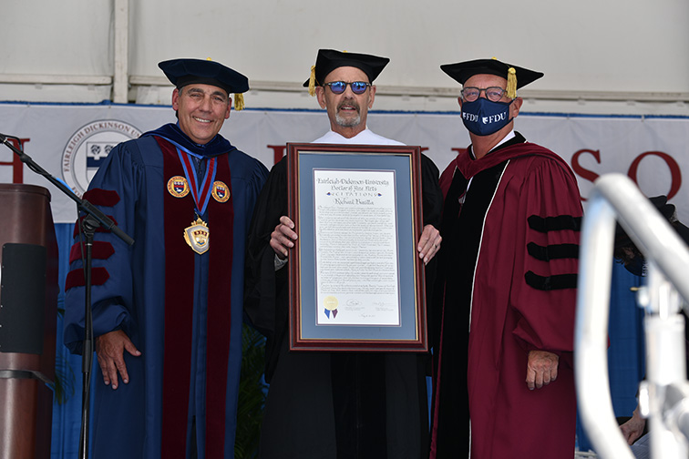 Richard Baratta stands with FDU administrators and shows off his honorary degree citation.