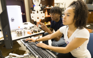 Two students work on a computer in a tech lab.
