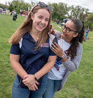Two students smile