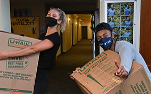 Two students haul huge boxes into a residence hall on move-in day.