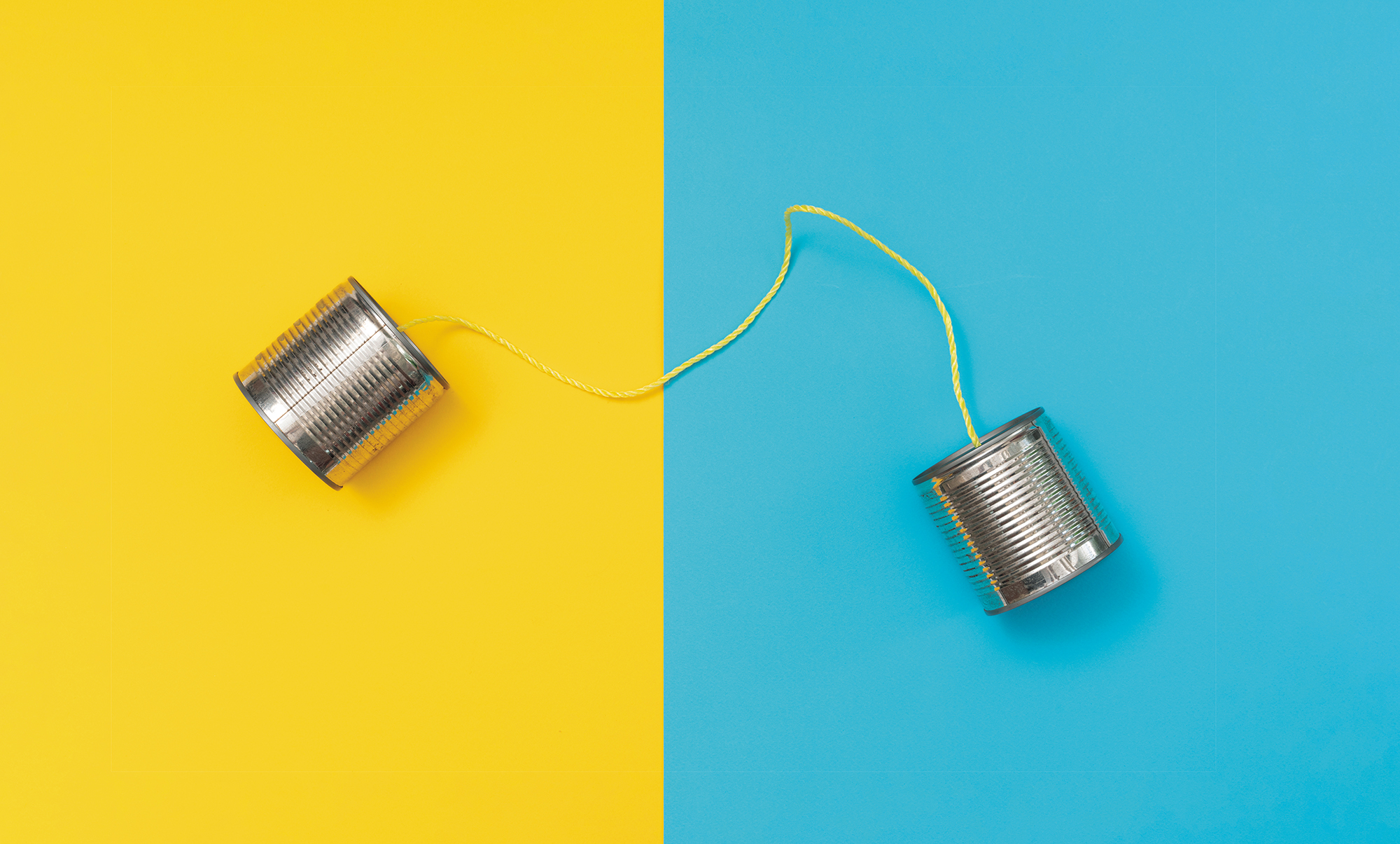 Tin can phone on yellow and blue paper backgrounds.