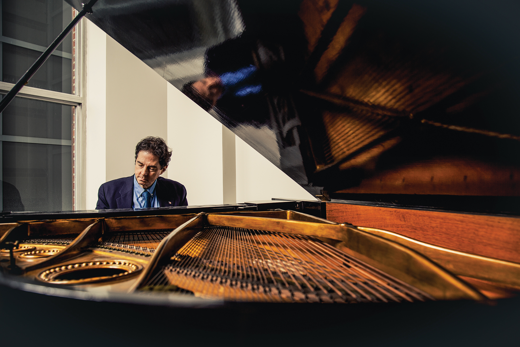 A man plays the piano wearing a suit.