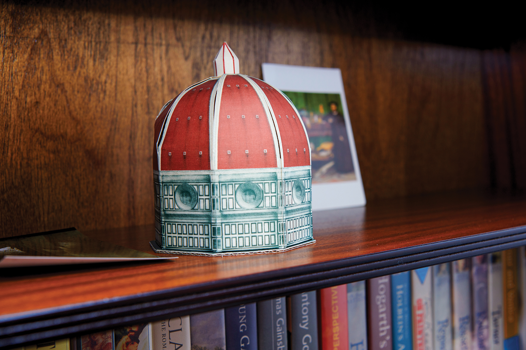 A miniature cardboard mock of the Duomo in Florence, Italy, sits on a bookshelf.