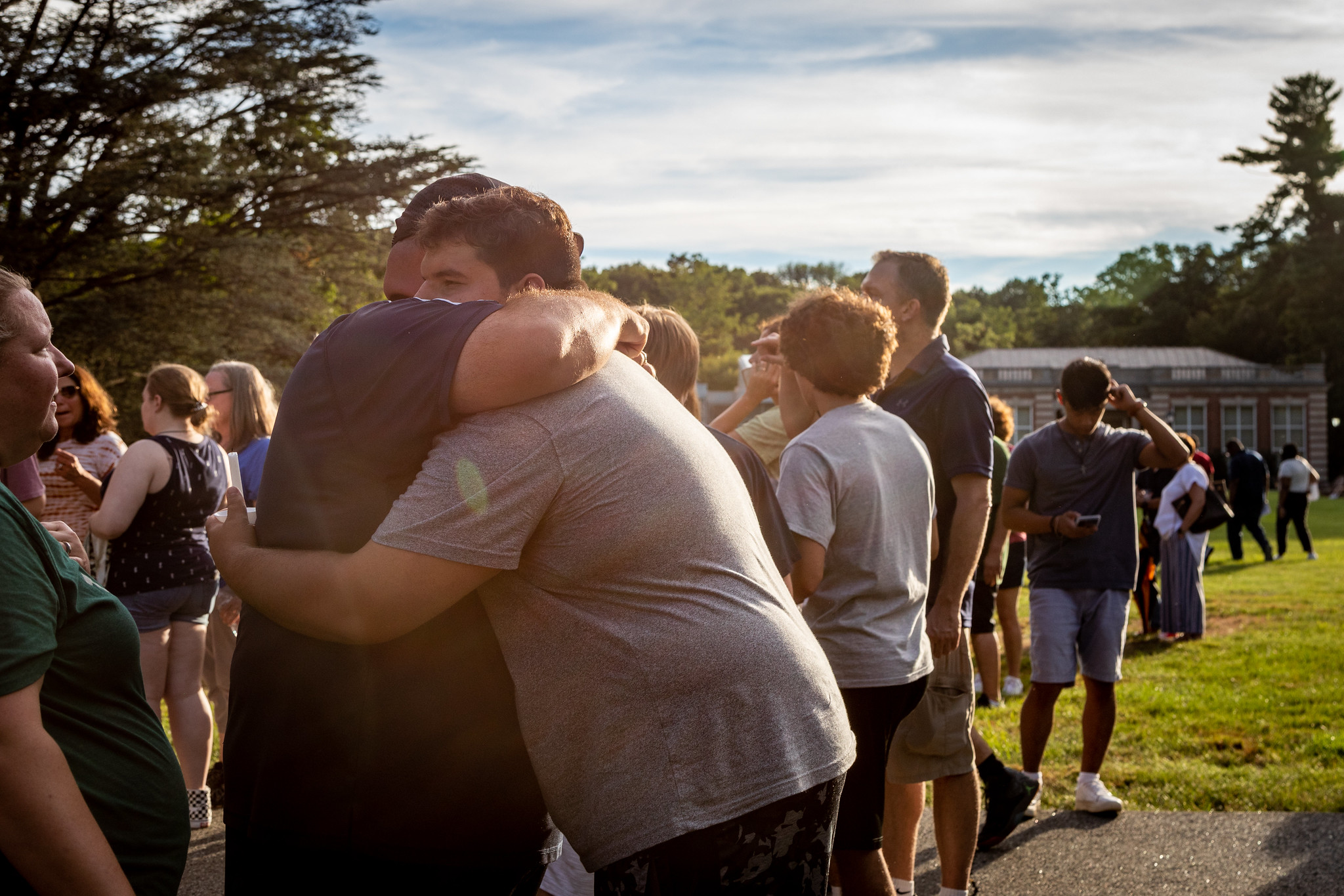 Families and students hug at a candlelight ceremony.