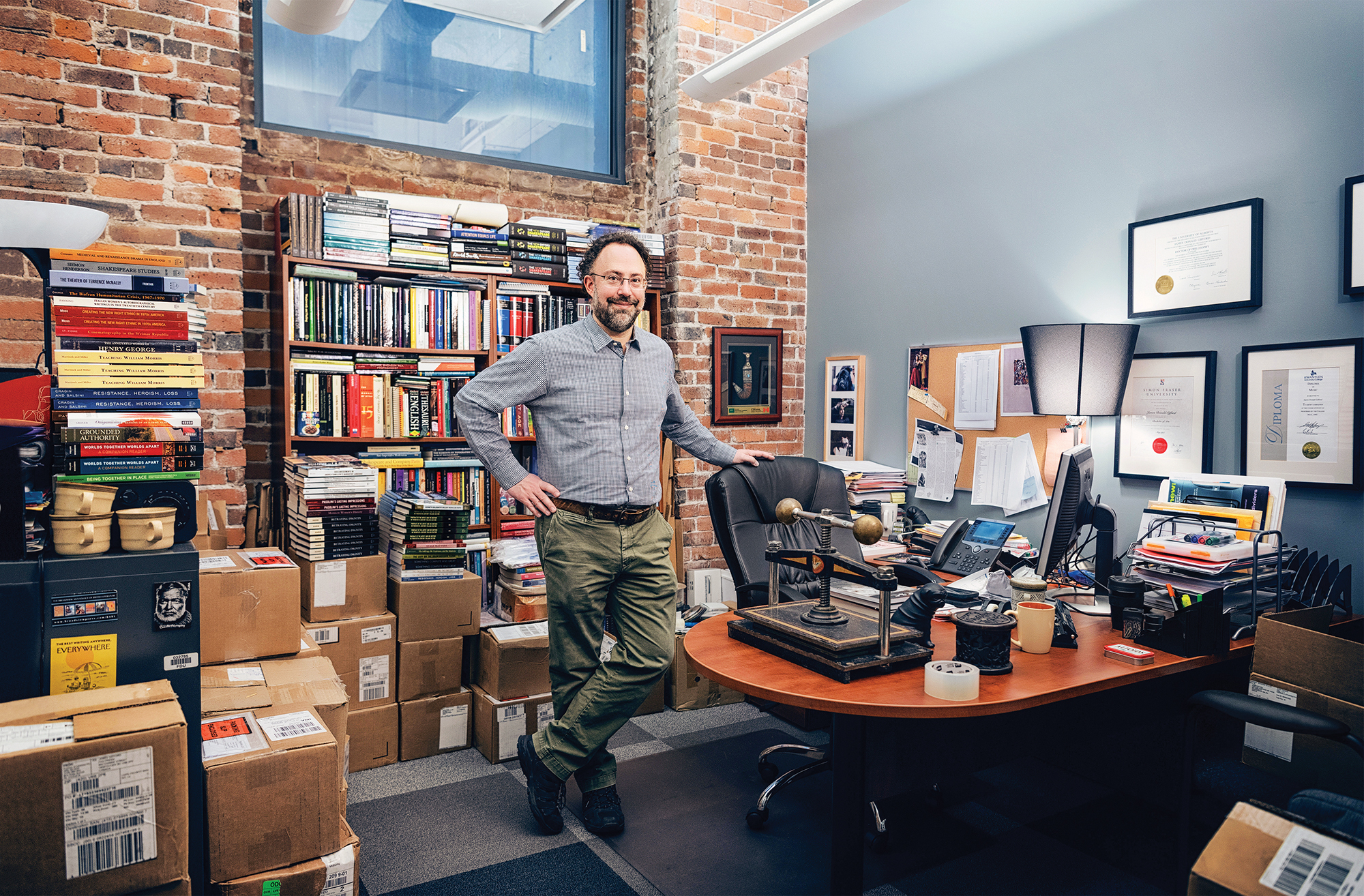 A male professor stands in his cluttered office.