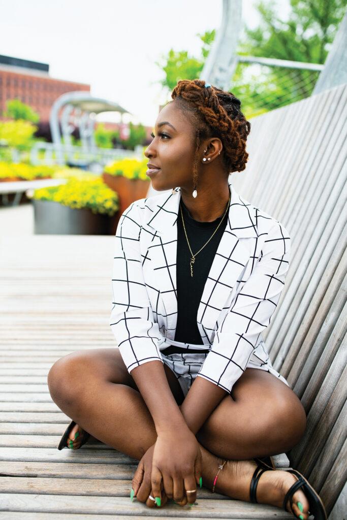 A young Black woman sits cross-legged on the Metro footbridge.