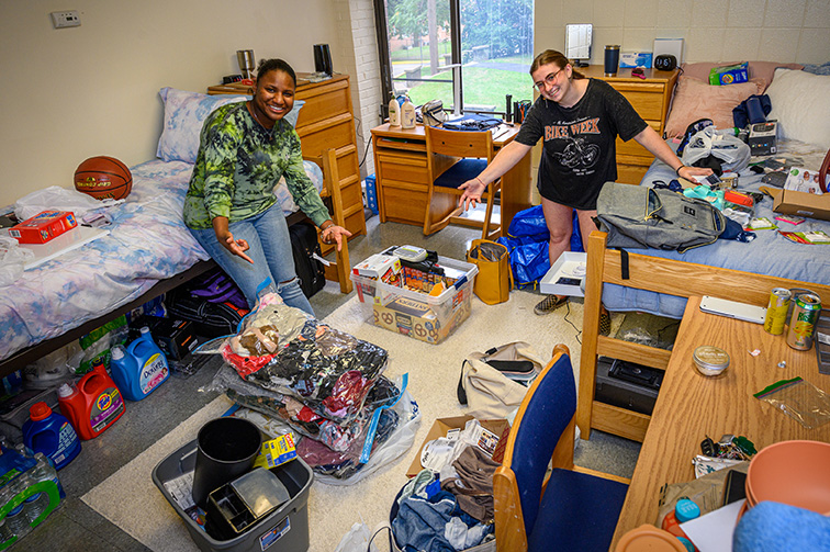 Two young women stand, arms out wide, in the middle of a messy dorm as they unpack.
