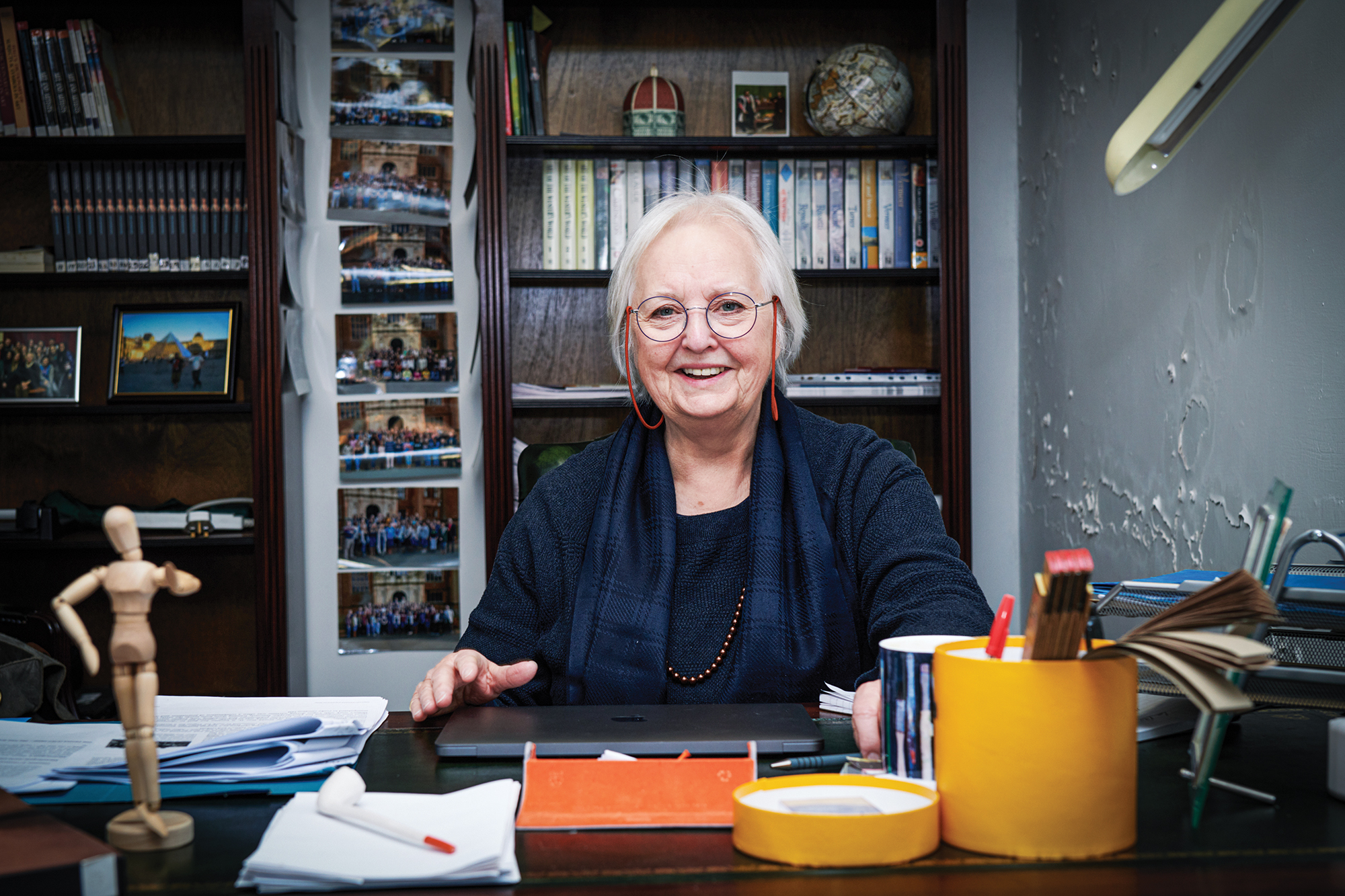 A female professor sits at her desk.