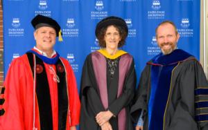 Three faculty members stand in full regalia.