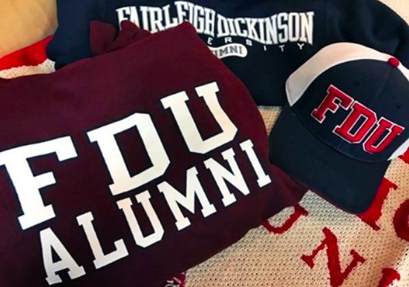 A pile of FDU alumni gear: a sweatshirt and hat and t-shirt.