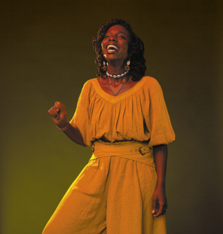 Portrait of a woman wearing a jumpsuit, in mid-laugh.