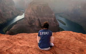A young woman wearing an FDU shirt looks out over Horseshoe Bend.