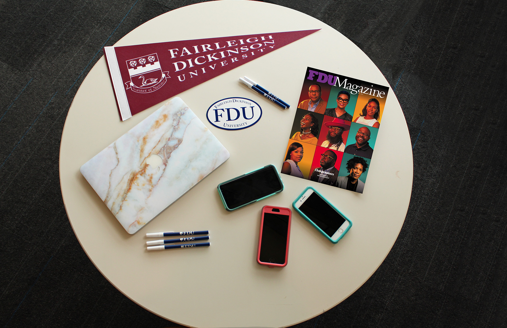 Still life of a table with an FDU pennant, a copy of FDU Magazine, three smartphones, a laptop and pens.