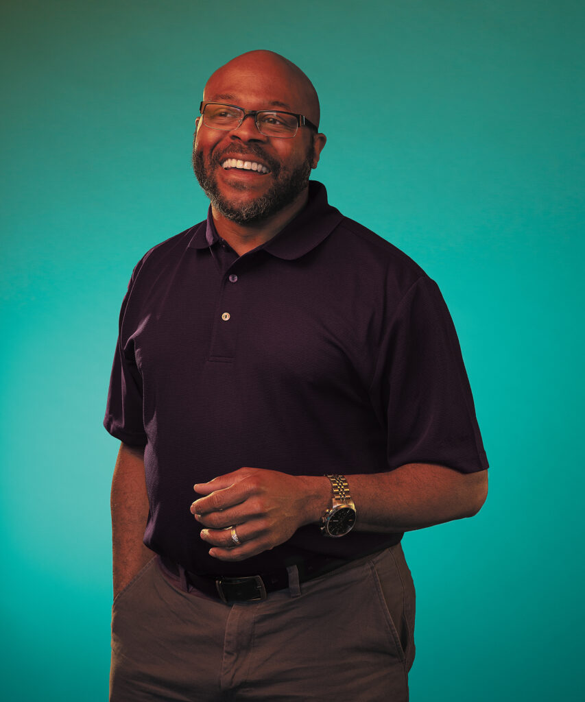 A man wearing glasses smiles broadly in a portrait photo.