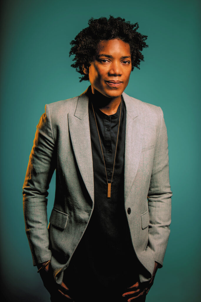 A portrait of a woman wearing a blazer, with her hands in her pockets.