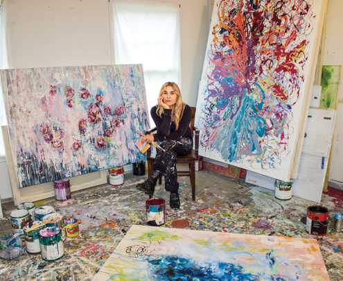 A female artist sits in her studio surrounded by her paintings and artwork.