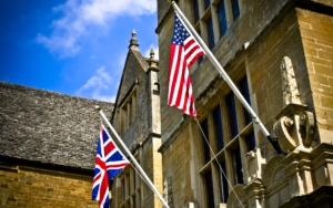 The facade of Wroxton Abbey, and the U.S. flag and the United Kingdom flag.