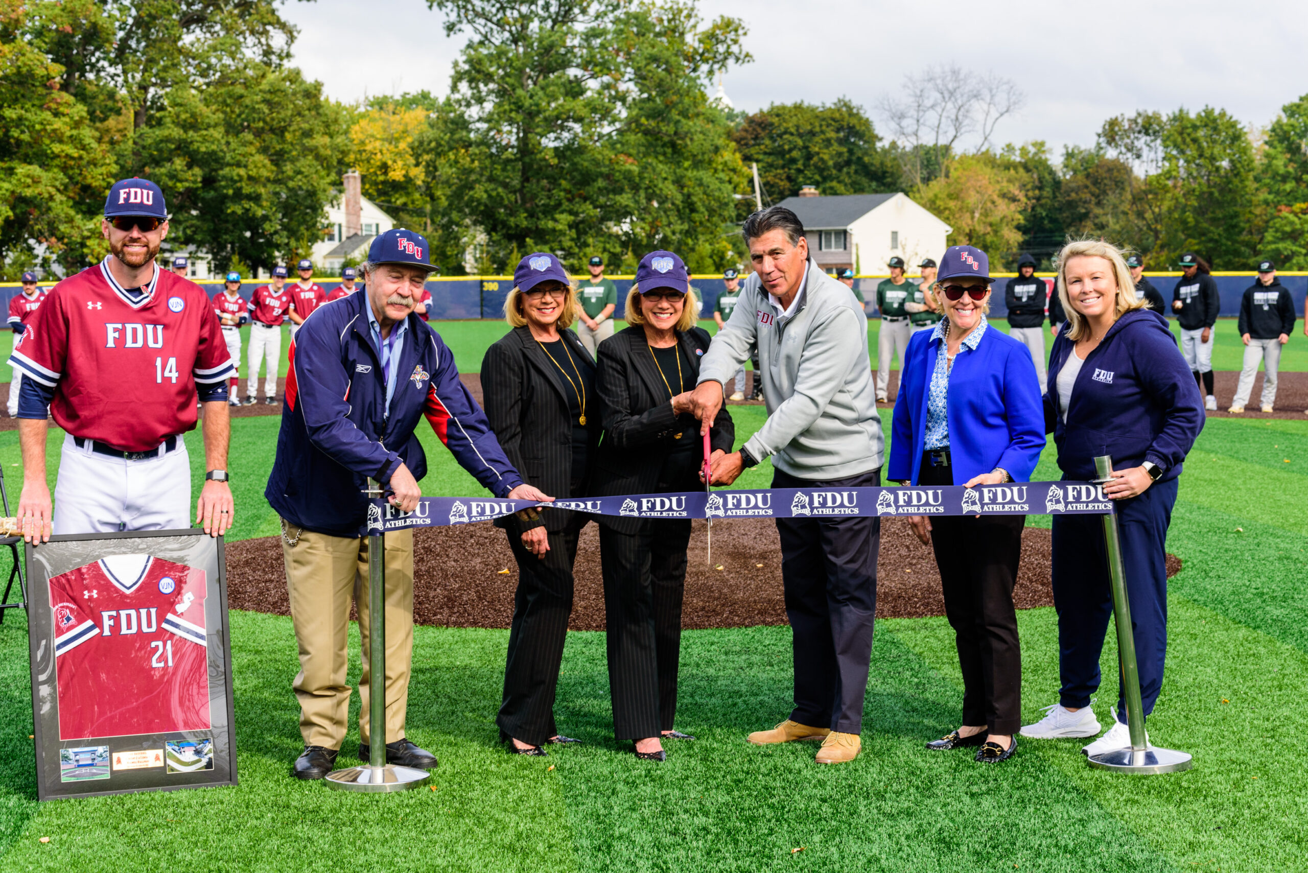 Dignitaries stand behind a ribbon about to be cut, to commemorate the opening of the Vincent J. and Lenda F. Naimoli Ballpark.