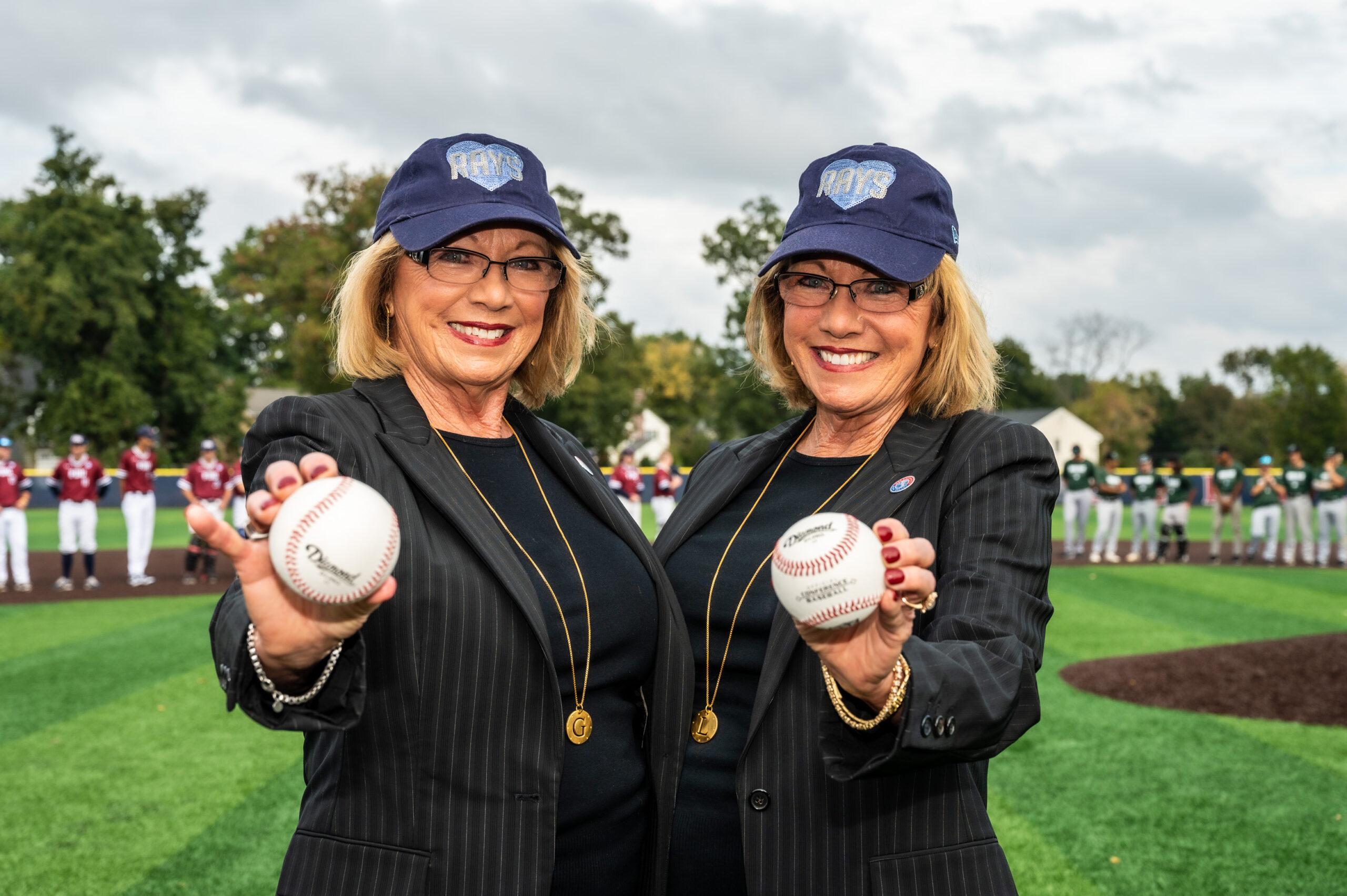 Two women hold baseballs.