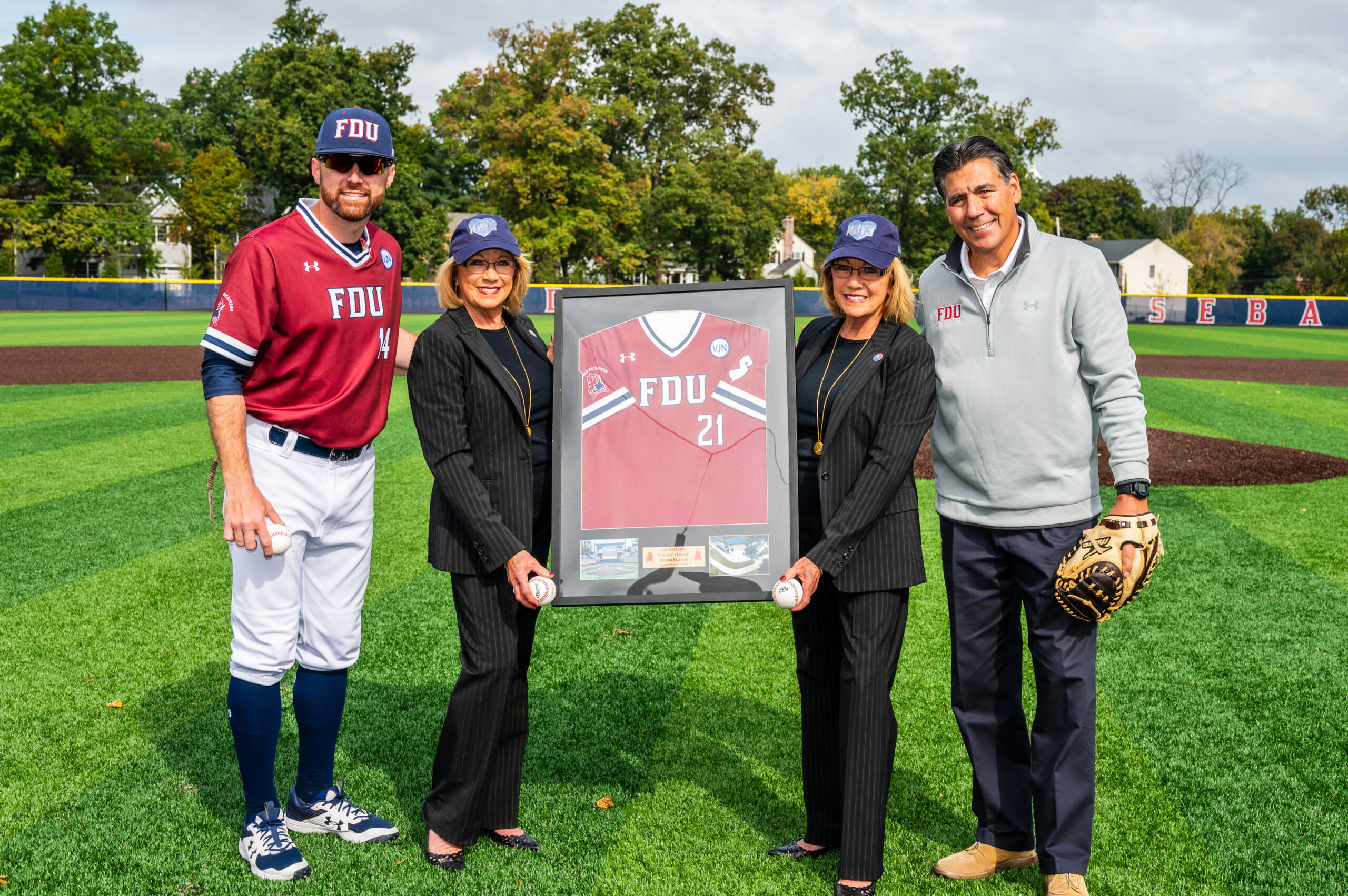 Two men and two women pose for a photo as the women hold a framed FDU baseball jersey.